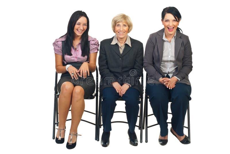 Risa de tres mujeres de negocios en silla imagenes de archivo