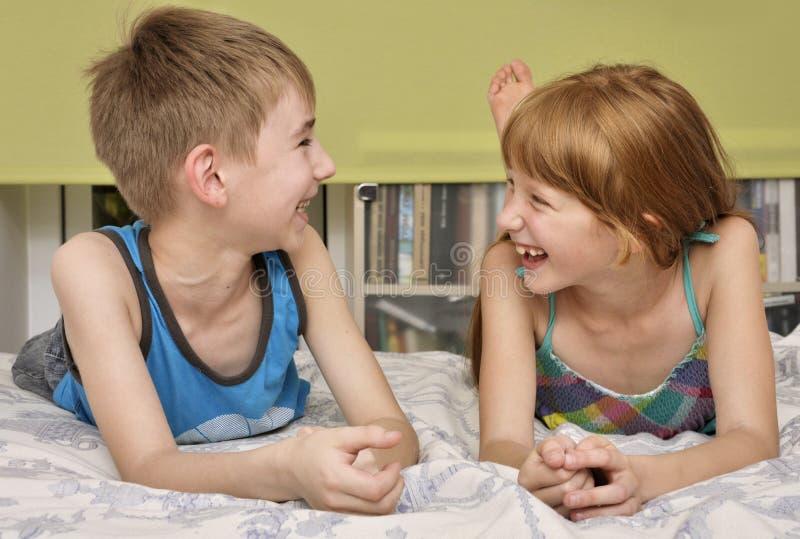 Risa del muchacho y de la muchacha imagenes de archivo