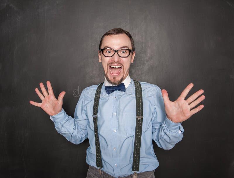 Risa divertida feliz del hombre del profesor en la pizarra fotografía de archivo