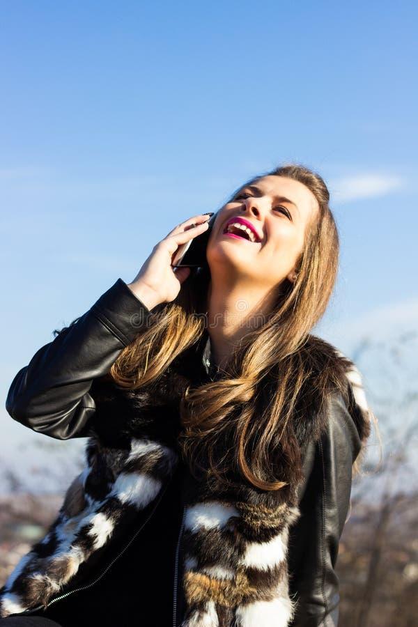 Risa femenina joven y el hablar en móvil imagen de archivo libre de regalías