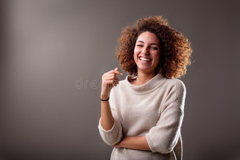 Risa suramericana rizada feliz de la mujer imagenes de archivo