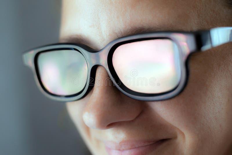 Risas de la muchacha en los vidrios 3D en un cine mientras que mira un primer de la forma de vida de la película foto de archivo libre de regalías