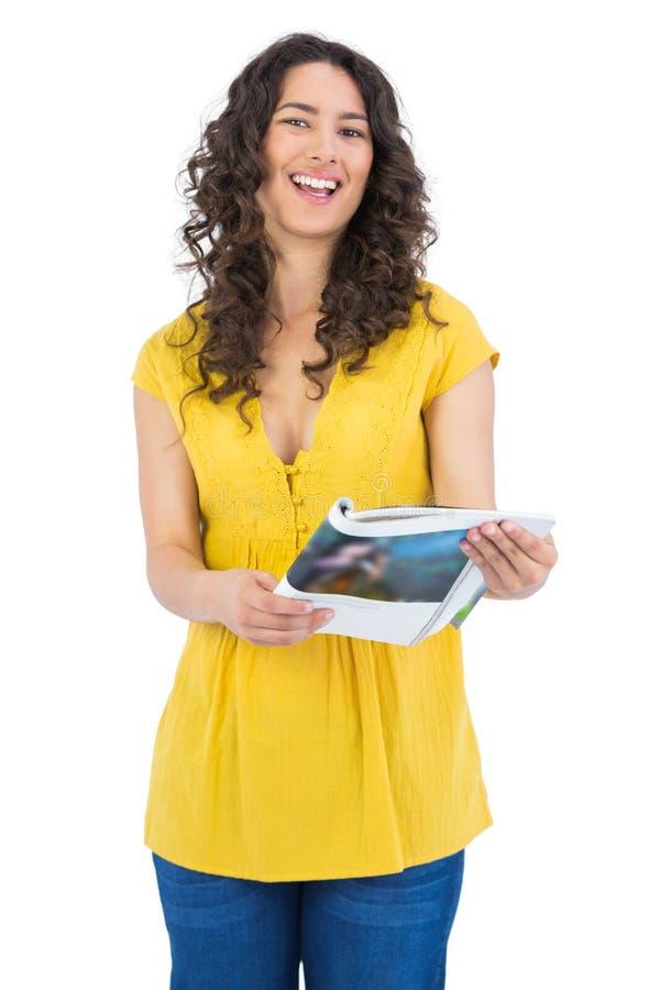 Risata castana dai capelli riccia mentre leggendo rivista fotografia stock libera da diritti