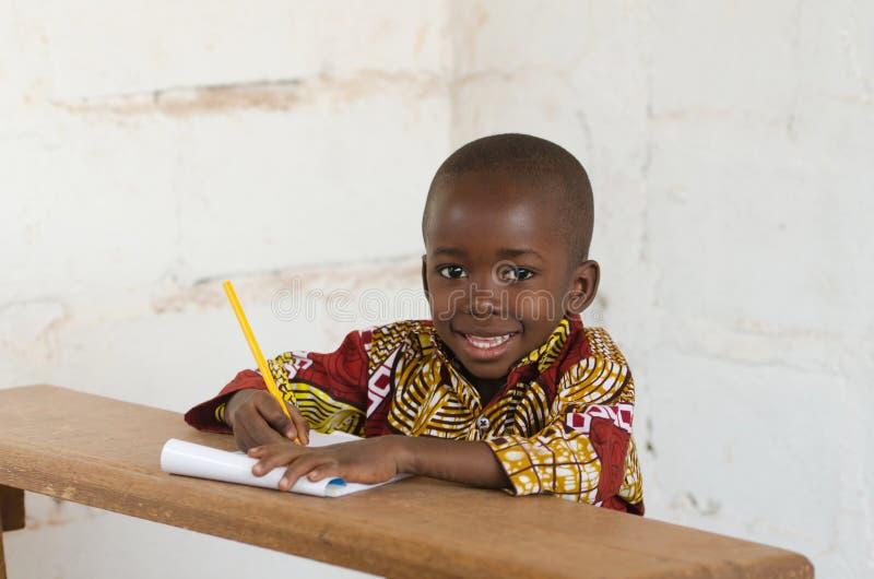 Risata del poco ragazzo di scuola africano che si siede in scrittorio che sorride al Ca immagine stock
