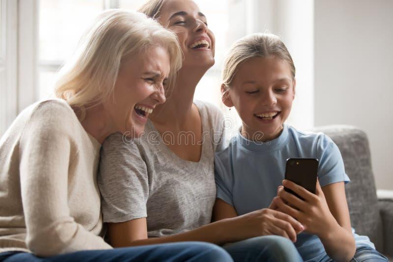 Risata delle tre generazioni di donne divertendosi facendo uso dello smartphone fotografia stock libera da diritti