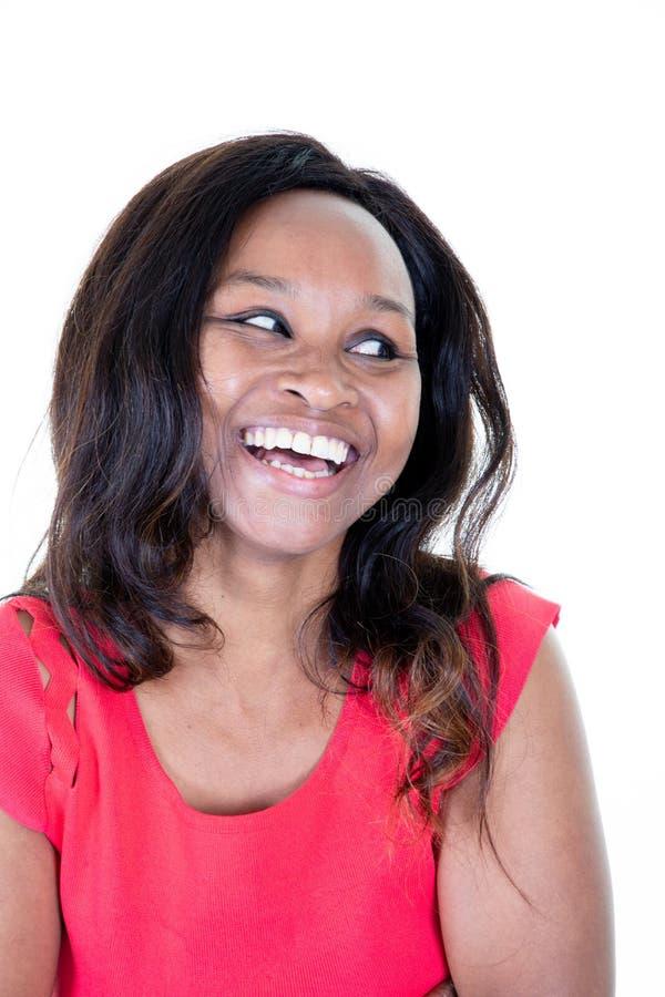 Risata sorridente incantante della donna 20s e guardare da parte isolato sopra l'afroamericano bianco del fondo fotografia stock