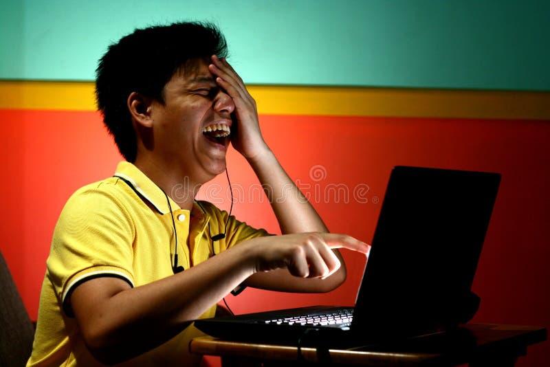 Risata teenager asiatica e lavorare ad un computer portatile fotografie stock