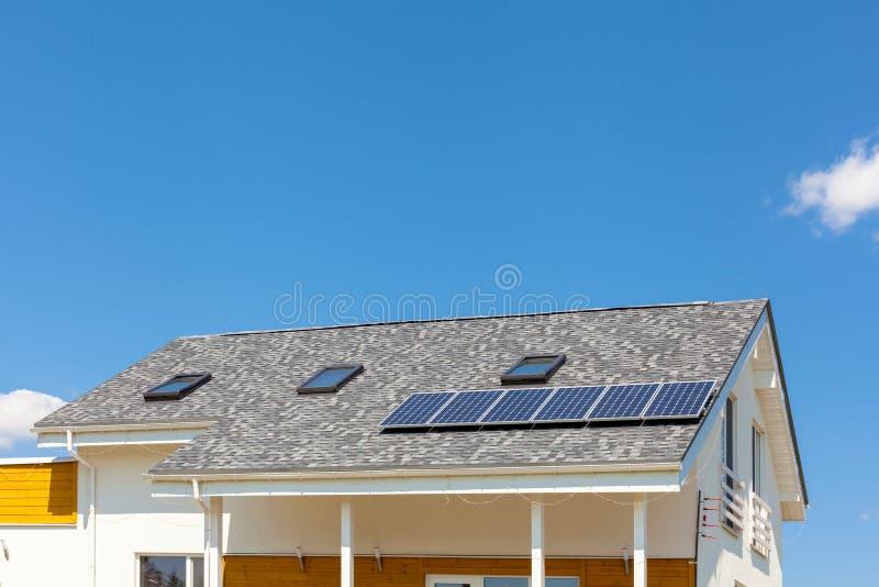 Riscaldamento di pannello solare dell'acqua sul tetto della nuova casa con i lucernari contro cielo blu fotografia stock