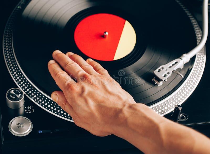 Risco da plataforma giratória, mão do DJ no registro de vinil imagem de stock