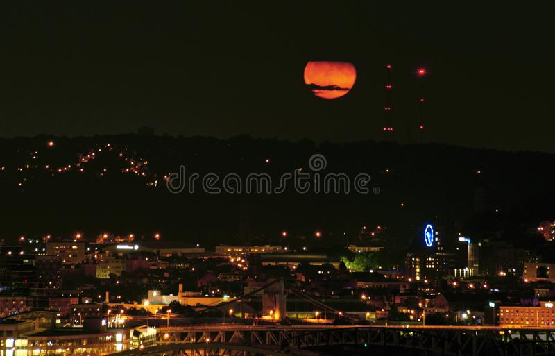 Rise of blood red moon. Rise of blood moon over urban landscape. Lunar eclipse royalty free stock photos
