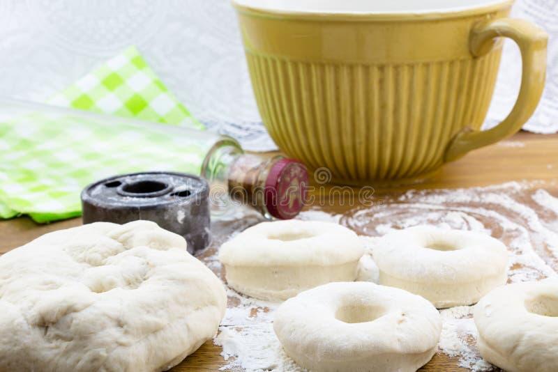 Risen doughnut dough on flowered wood table with cutter and rolli. Risen doughnut dough on flowered wood table with vintage metal doughnut cutter and glass stock photos