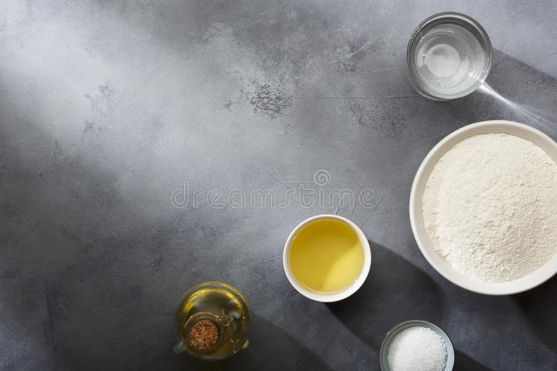 Risen or proved yeast dough for bread or pizza on a floured slate surface. Top view stock photos