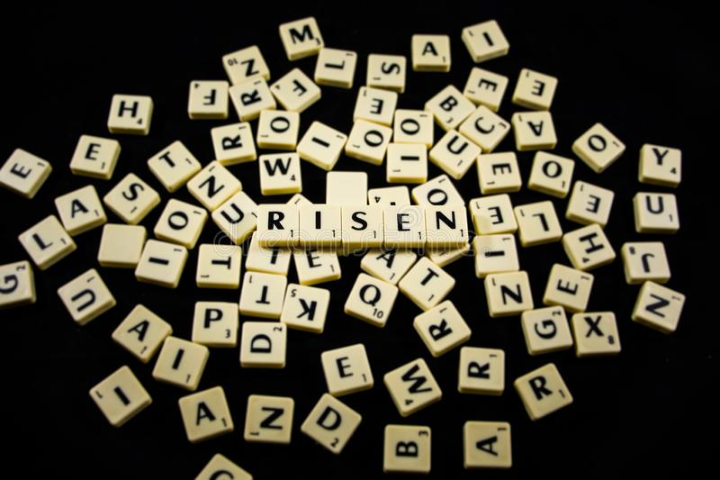 Risen word spelled with letter tiles in black background royalty free stock photos
