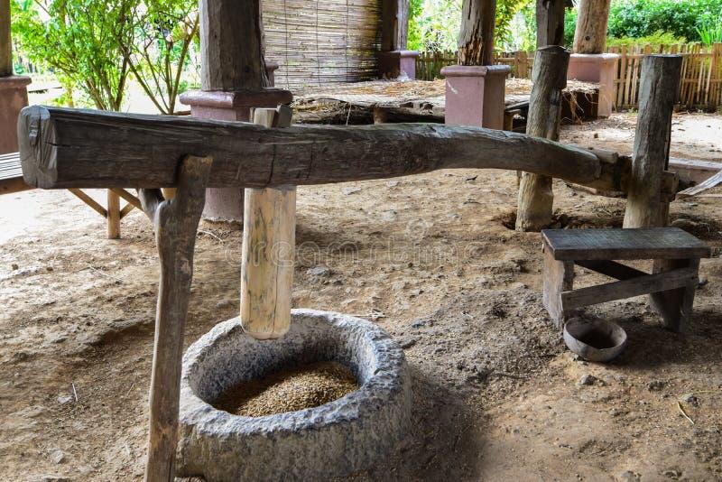 Riseria tradizionale con un mortaio e un pestello di legno, cultura fatta a mano di legno del mortaio del riso, metodo tradiziona immagine stock libera da diritti