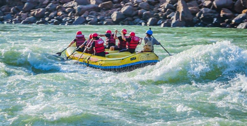 Rishikesh, Índia - os jovens em transportar de rio da água branca da aventura estão apreciando esportes de água no rio Ganges imagens de stock royalty free