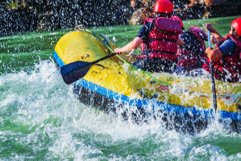 Rishikesh, Индия - молодые люди на сплавлять реки белой воды приключения наслаждаются водными видами спорта в реке Ганге стоковое фото