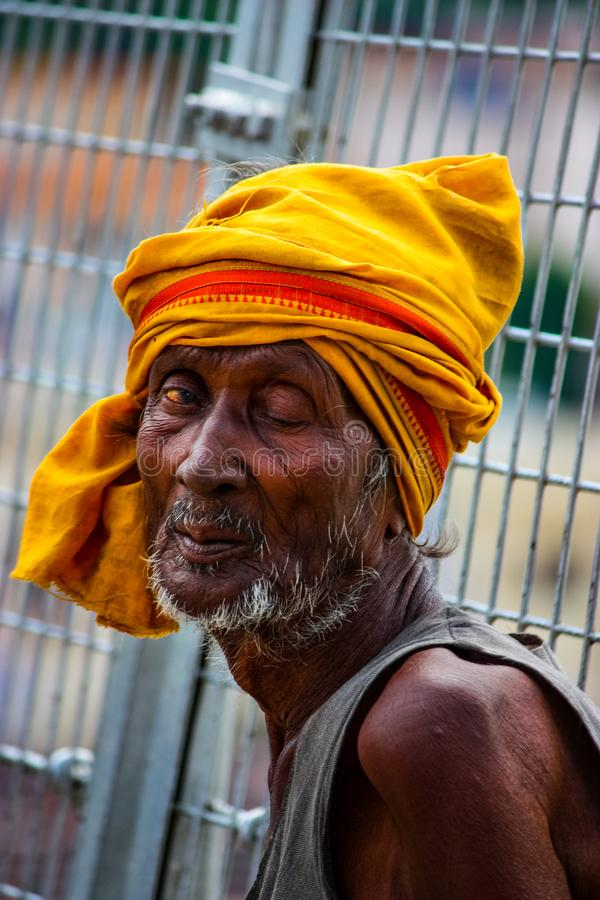 Rishikesh, India - August 20, 2009: close up of a beggar face with half-open eyes in Rishikesh, Uttarakhand, India royalty free stock images