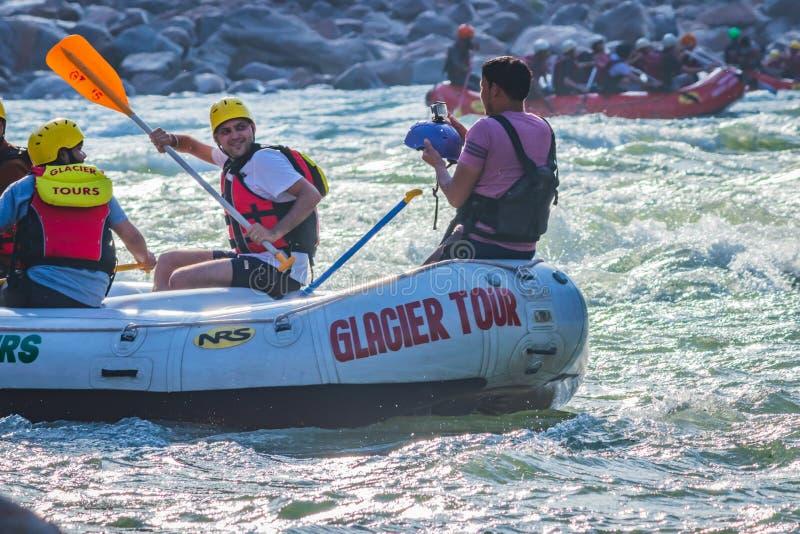 Rishikesh, India - i giovani sul rafting del fiume dell'acqua bianca di avventura stanno godendo degli sport acquatici in fiume G fotografie stock libere da diritti