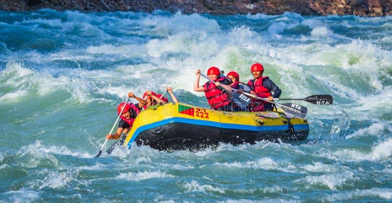 Rishikesh, India - i giovani sul rafting del fiume dell'acqua bianca di avventura stanno godendo degli sport acquatici in fiume G fotografia stock libera da diritti