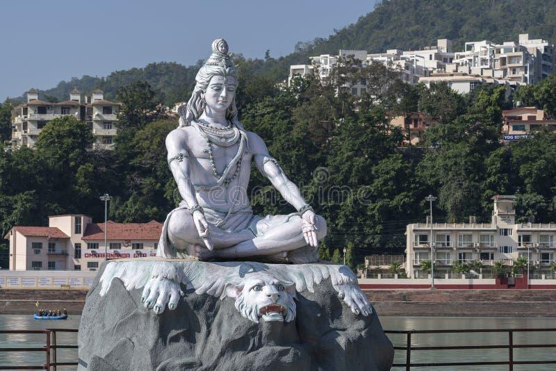 Statue of Shiva, Hindu idol near Ganges River water, Rishikesh, India. The first Hindu God Shiva. Sacred places for pilgrims stock image