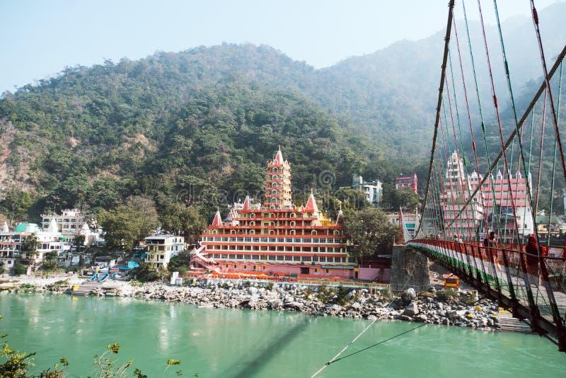 Rishikesh Indien 10. Januar 2018 Schöne Ansicht des Ganga-Flussdammes, der Brücke Lakshman Jhula und der Tera Manzil Temples, Tra stockfoto