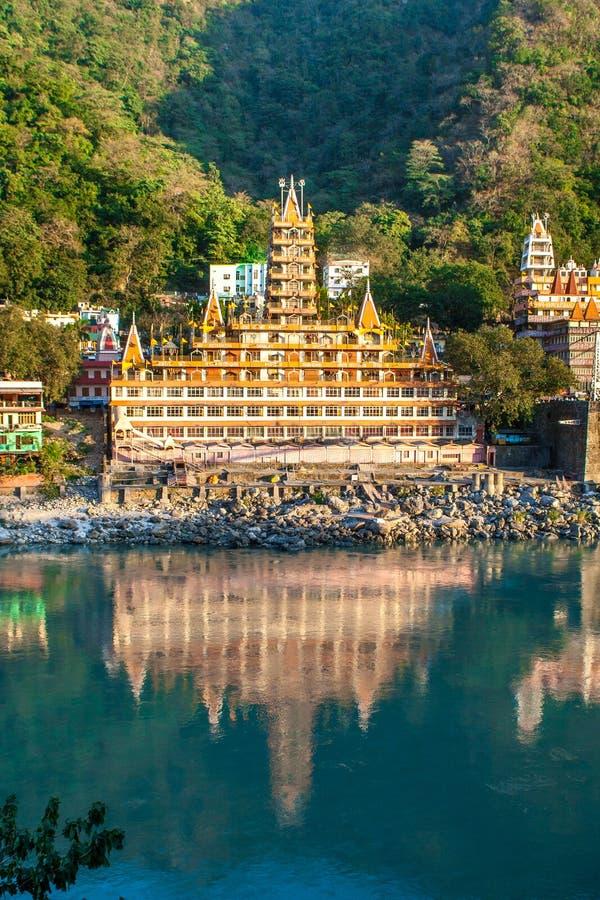 RISHIKESH INDIEN - Noveber 2012: Tera Manzil Temple sikt från den annan Ganga banken med en spegelreflexion i vattnet royaltyfria foton