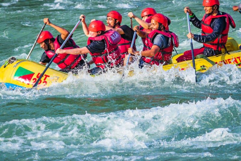 Rishikesh, ?ndia - os jovens em transportar de rio da ?gua branca da aventura est?o apreciando esportes de ?gua no rio Ganges imagens de stock royalty free