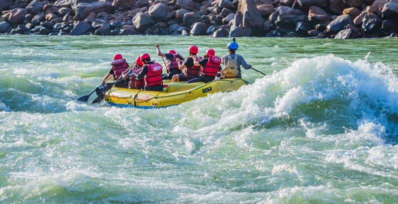 Rishikesh, ?ndia - os jovens em transportar de rio da ?gua branca da aventura est?o apreciando esportes de ?gua no rio Ganges imagem de stock