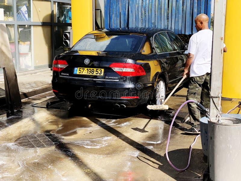 Rishon Le Сион, Израиль - 27-ое февраля 2018: Укомплектуйте личным составом мытье автомобиль вручную используя подготовку для пол стоковые фото