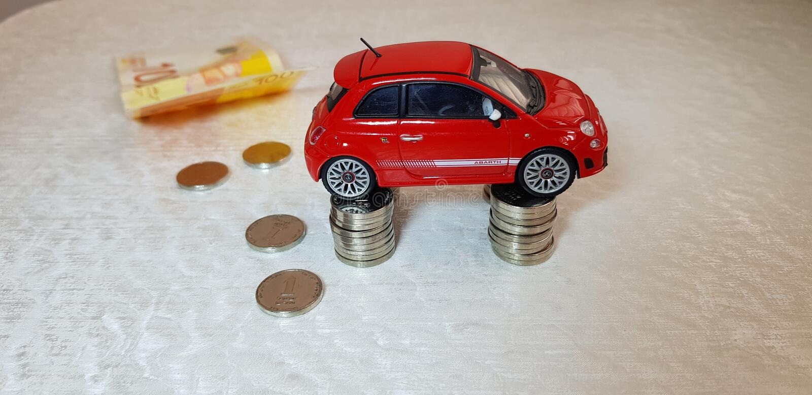 Small red fiat 500 abarth toy stands on four columns of one Israeli shekel coins stock photography