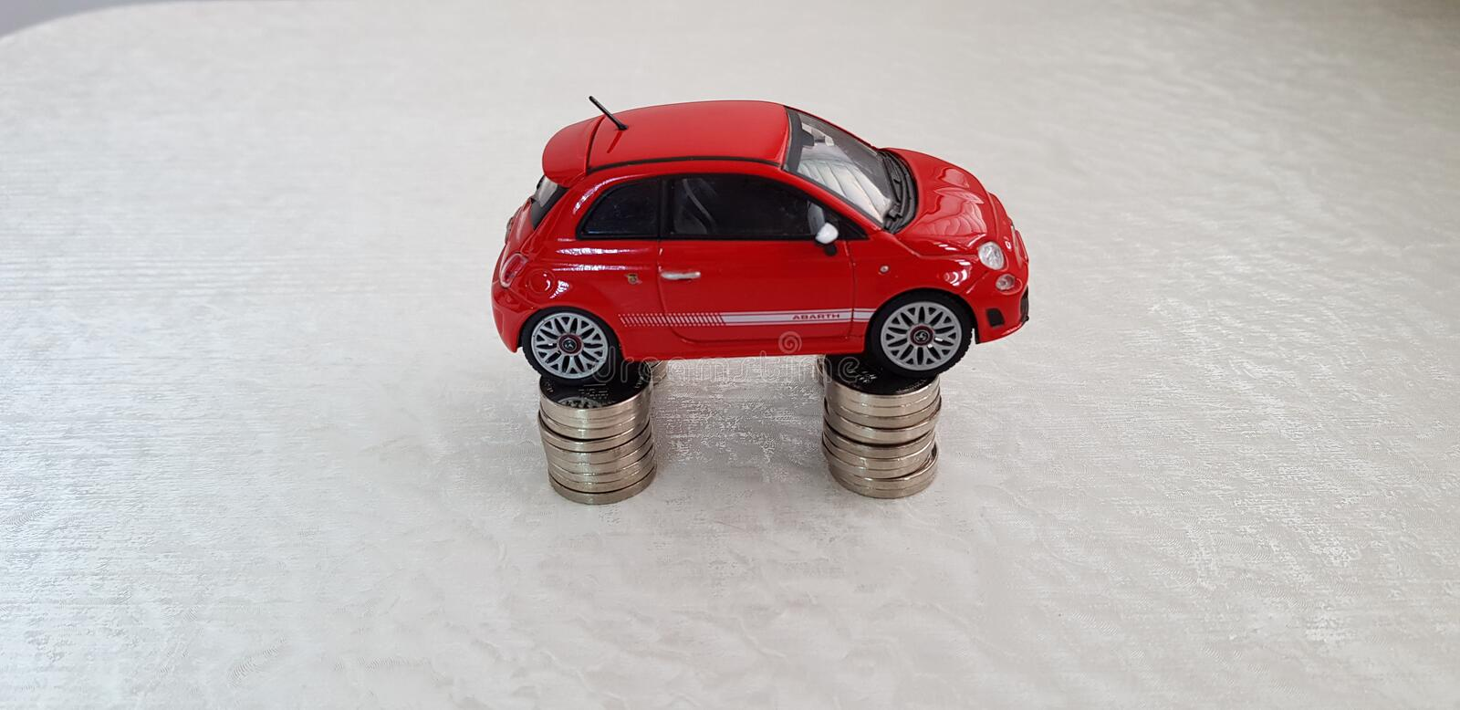 Small red fiat 500 toy stands on four stacks of one Israeli shekel coins royalty free stock images