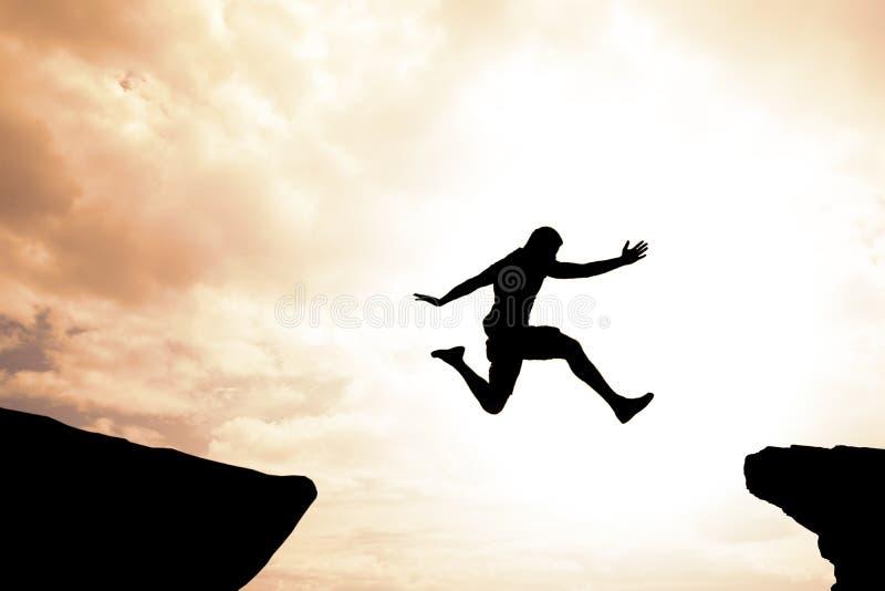 Risico en succesconcept de moedige zekere mens die over hiaat springen royalty-vrije stock afbeelding