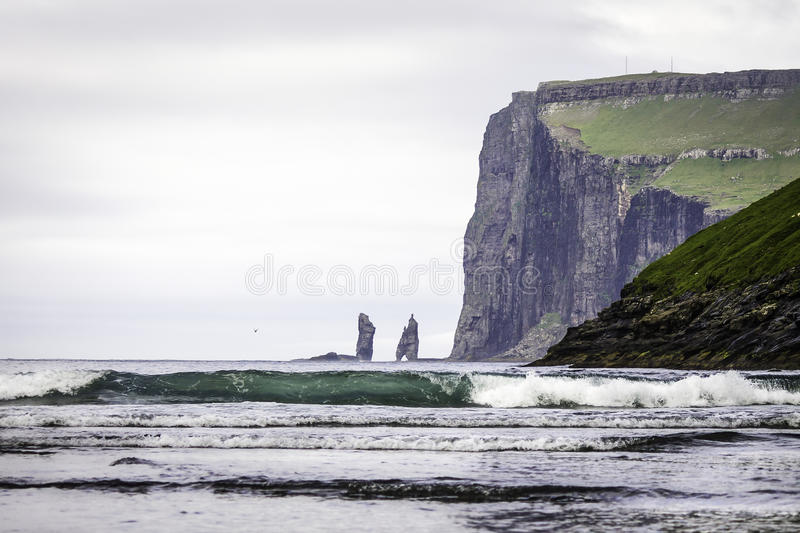 Risin and Kellingin sea stacks in the distance, with a big Wave approaching Tjornuvik bay, Streymoy, Faroe Islands (Faroes&# stock images