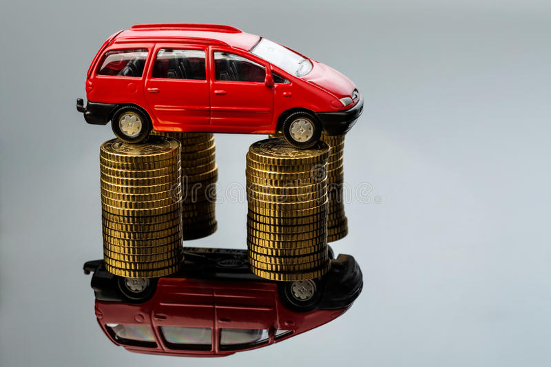 Rising car costs. car on coins. Increasing costs for the car through workshop costs stock image