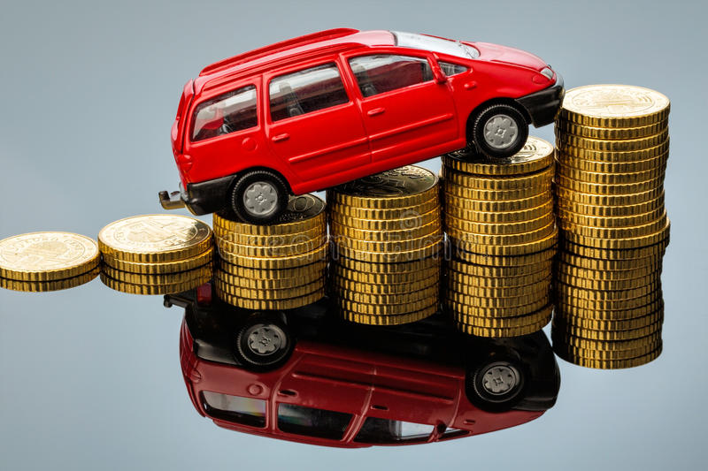 Rising car costs. car on coins. In a car you have rising costs through fuel, insurance, parking fees and tolls stock images
