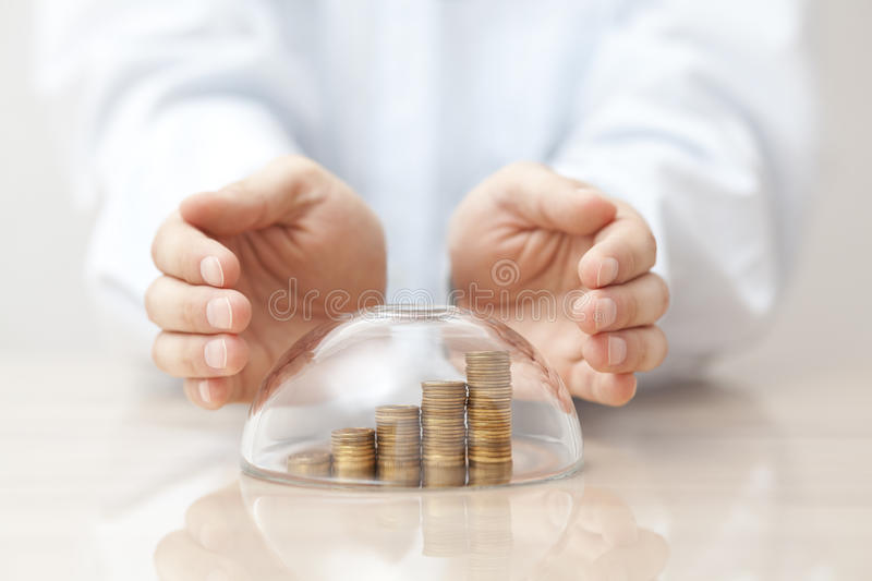 Rising coins protected under a glass dome and hands stock photos