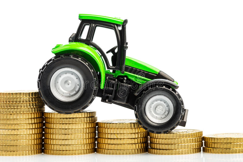 Rising costs in agriculture. Farmers in agriculture have to reckon with rising costs. higher preies in feed, fertilizer and plants. tractor with coins royalty free stock photos