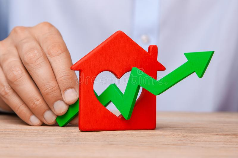 Rising house prices. Man is holding green arrow up in hand and house on the table royalty free stock photography