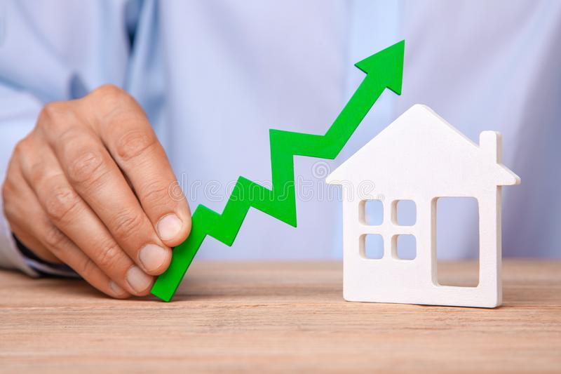 Rising house prices. Man is holding green arrow up in his hand and house stock photos
