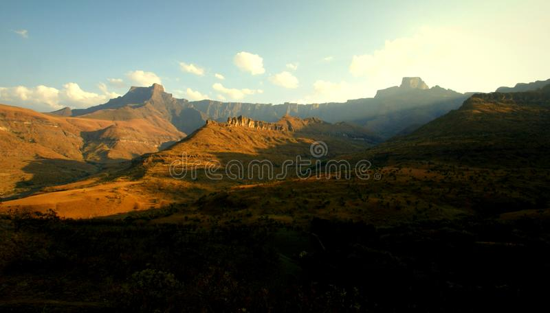 Rising morning sun at Drakensberg mountains, South Africa. Morning sun shining on the `amphitheater` mountain group, popular by tourists for hiking. SONY DSC royalty free stock image