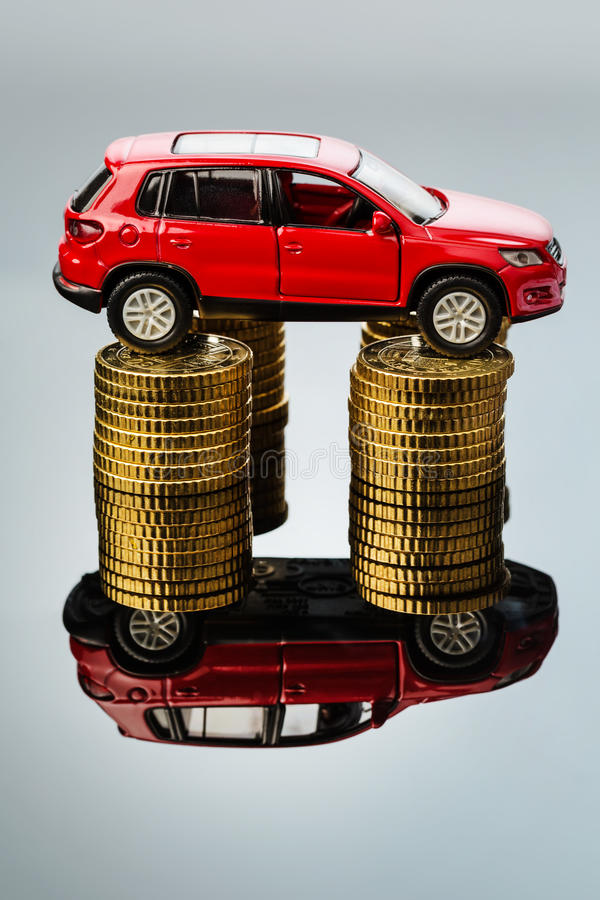 Rising motoring costs. car on coins. Rising cost of the car by workshop costs royalty free stock images