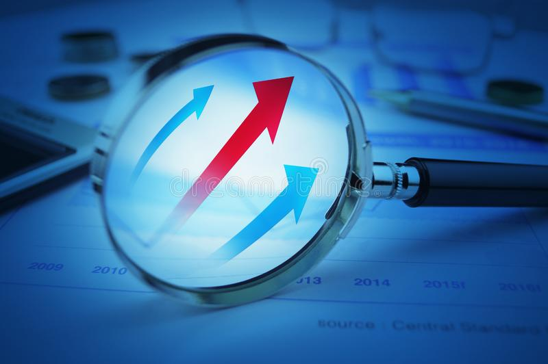 Rising red and blue arrow on magnifying glass over graph royalty free stock images