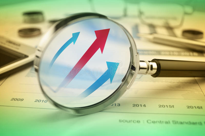 Rising red and blue arrow on magnifying glass over graph stock photo
