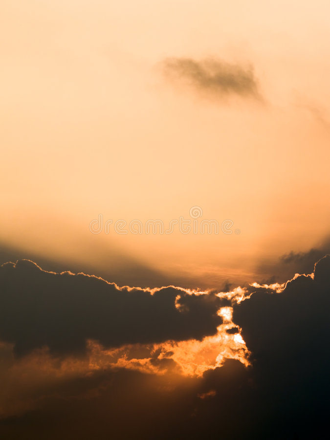 Rising Sun. THe rising sun just obscured by a patch of low clouds in the morning sky stock image
