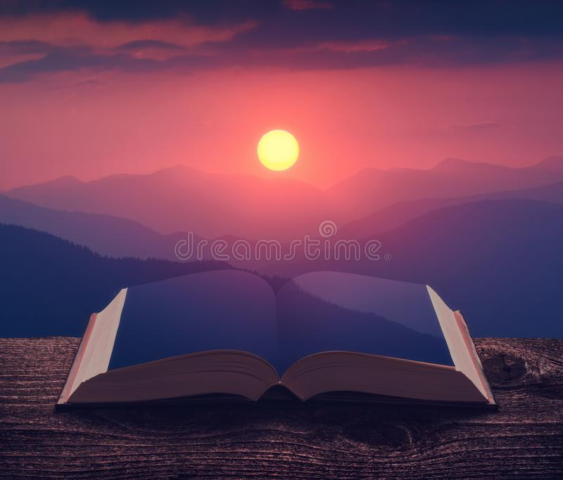 Rising of the sun above the blue mountains on the pages of book stock image