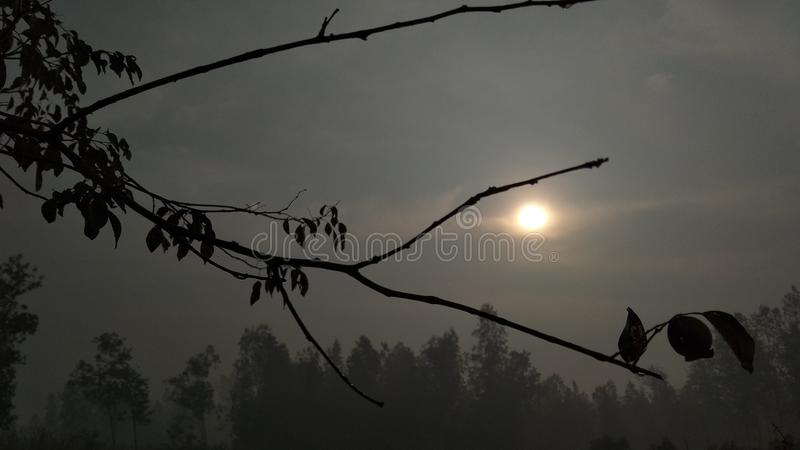 Is the rising sun. And cloudy sky stock image