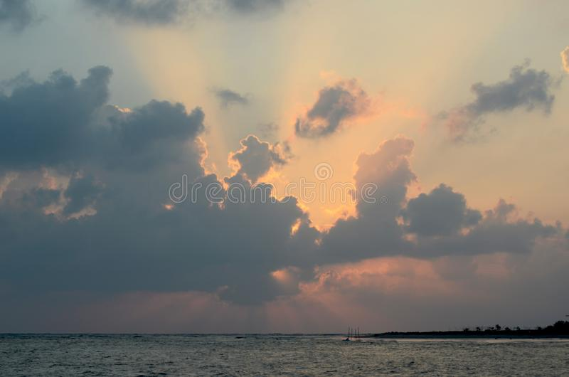 The rising sun hidden behind clouds above the ocean. Rays of light from the rising sun emerge from behind dark clouds. The sun is hidden. A tree-covered headland royalty free stock photos