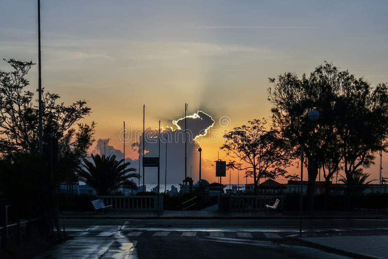 The rising sun. Illuminates the clouds over the silhouettes of the subtropical city landscape stock image