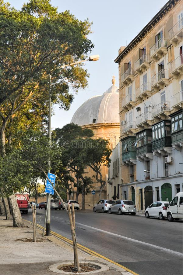 Floriana, Malta, August 2019. City street and the dome of a large cathedral in the early morning. The rising sun illuminates with its rays a large dome of a royalty free stock photos
