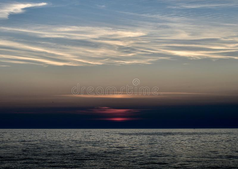 A Rising Sun Through Marine Layer #1. This is an early morning Summer picture of a rising sun through the marine layer on Lake Michigan off Diversey Harbor stock photos